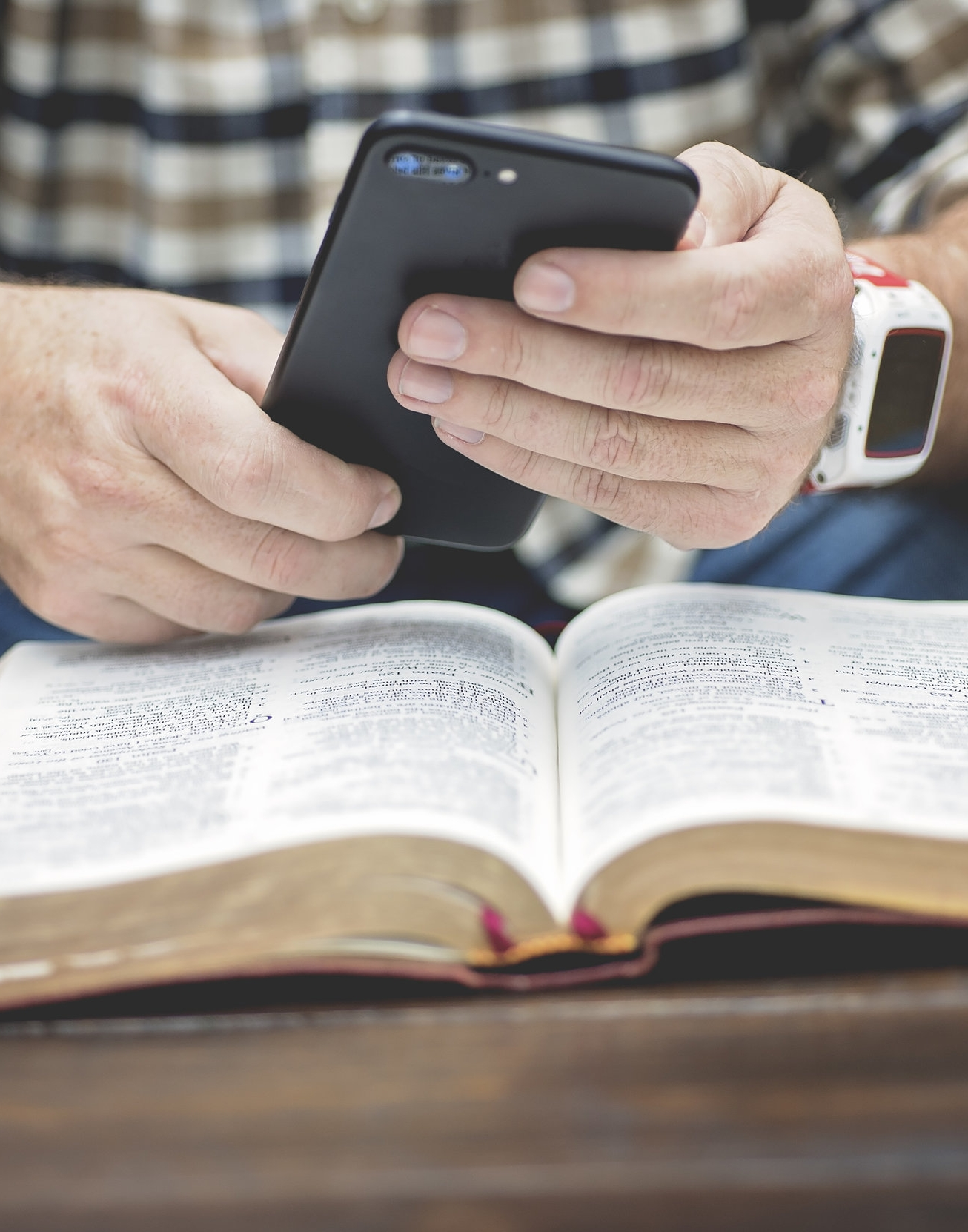 man texting on iphone over bible.jpg