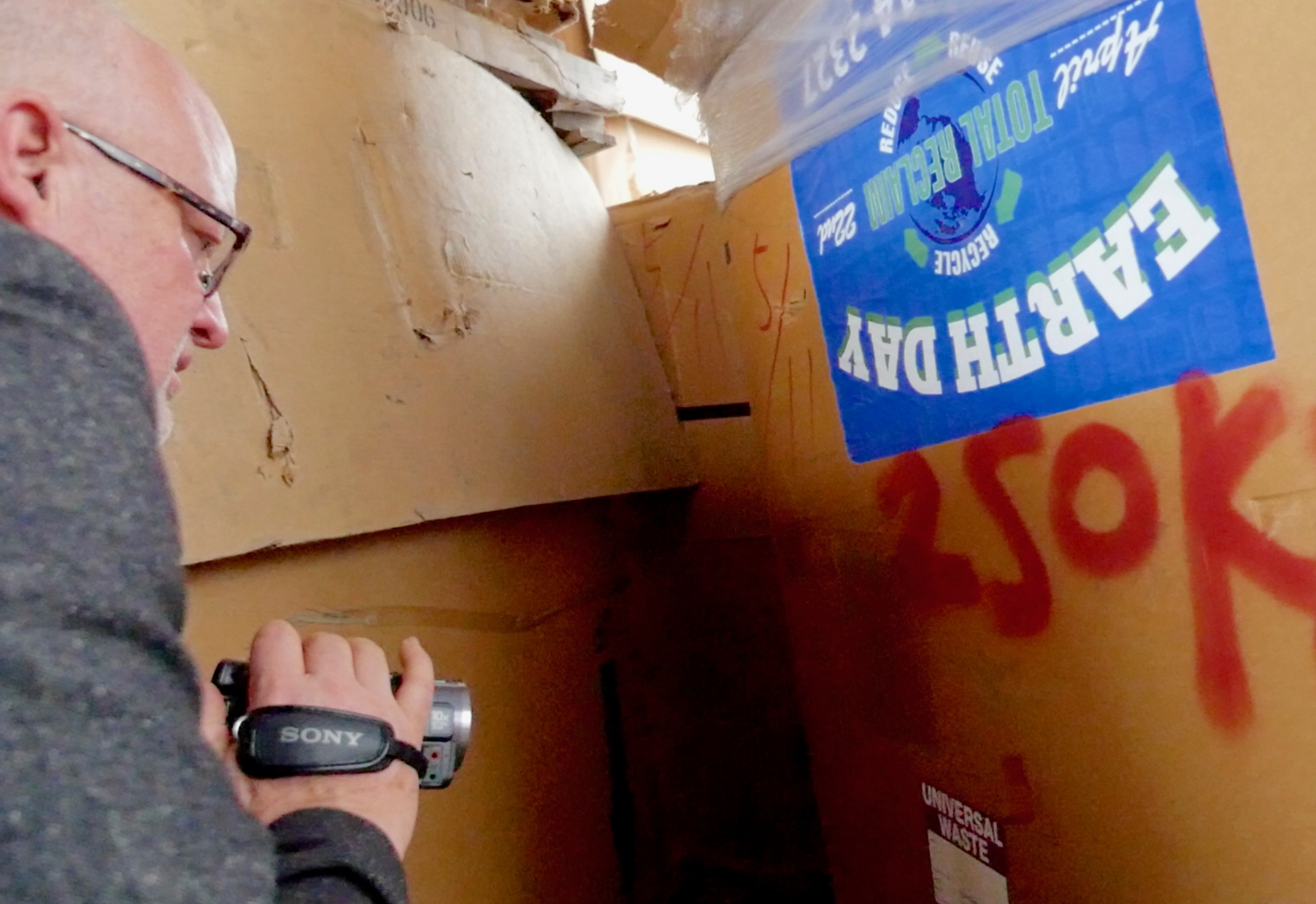 BAN's Jim Puckett documenting Total Reclaim's exports in Hong Kong electronics junk yard to prove that their export denials were false. Note Total Reclaim's Earth Day collection event stickers. Copyright PBS. March 2016.