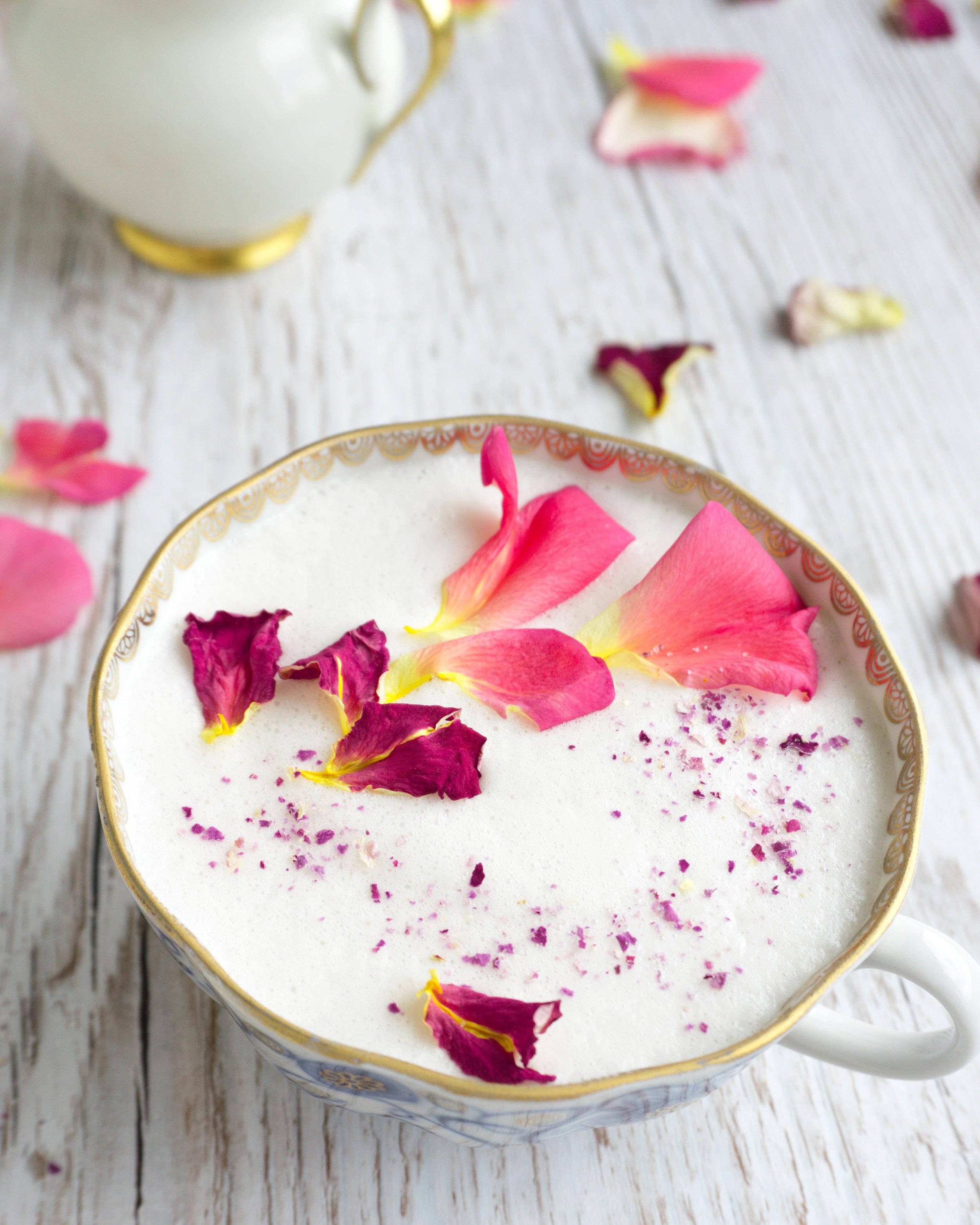 Du brauchst: - 1 Tasse Pflanzenmilch (z.B. meine schnelle selbstgemachte Nussmilch)1 Esslöffel Rosen-SirupOptional: etwas Rosen-Zucker und getrocknete und/oder frische Rosen-Blütenblätter zum Dekorieren