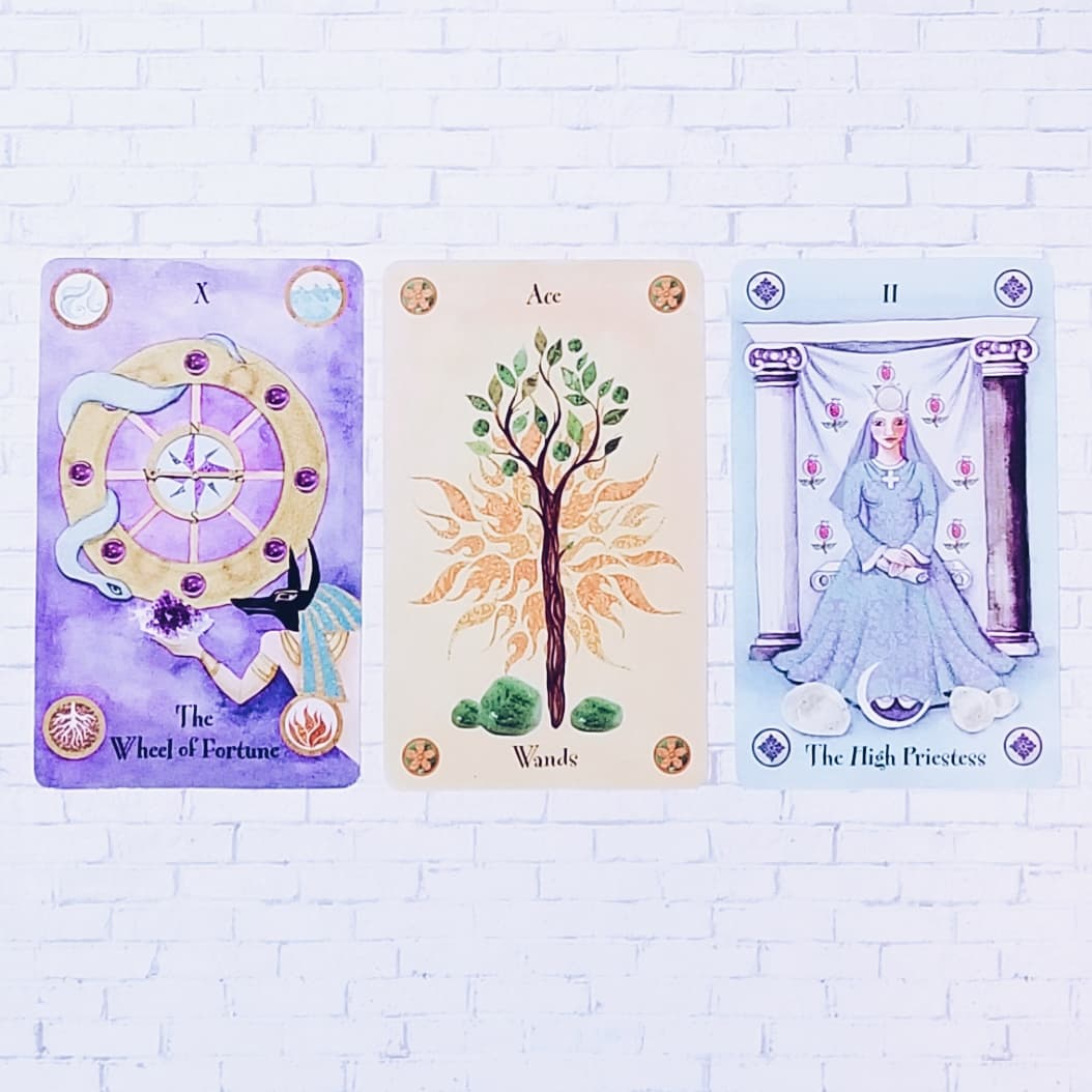 From left to right: The World,  Ace of Wands, The High Priestess