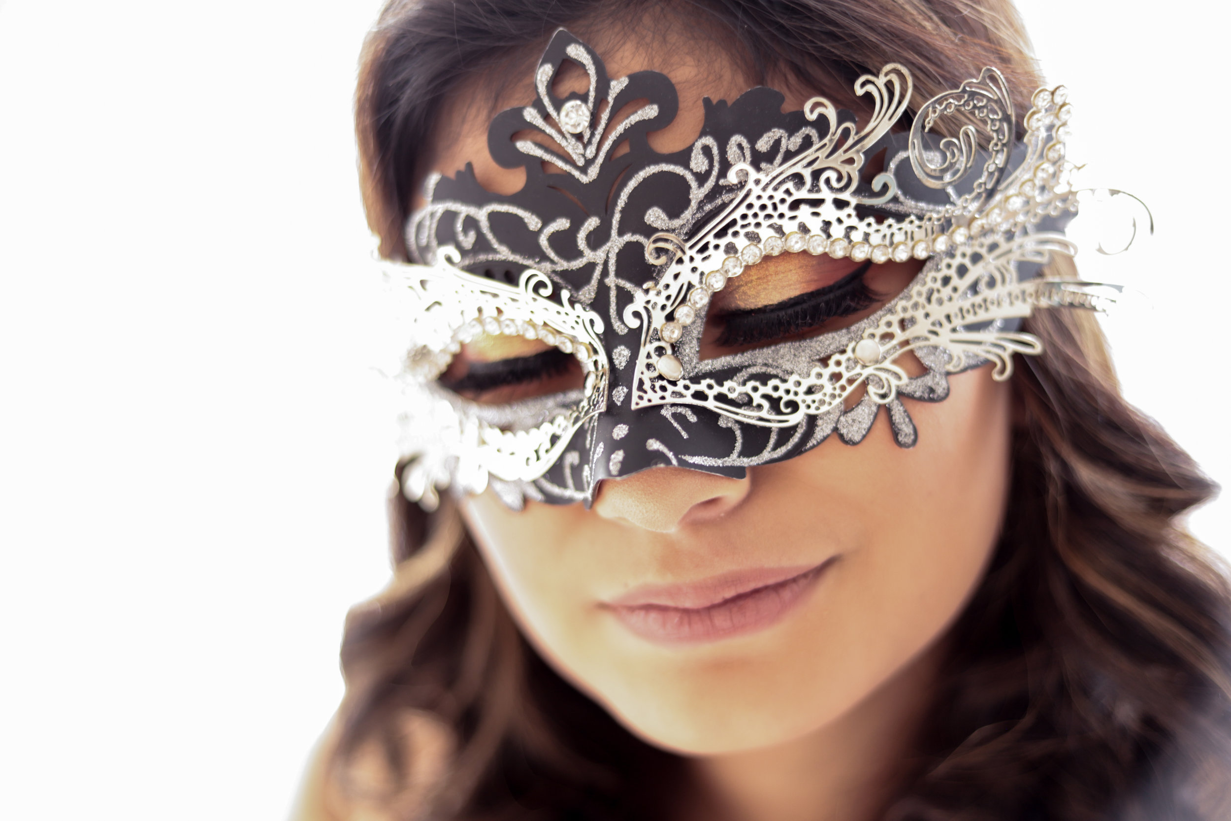 Woman in black and silver mardi gras mask with eyes closed