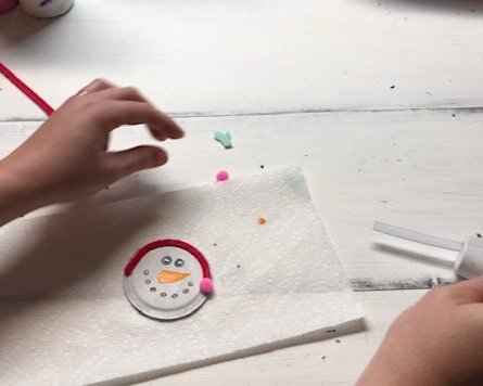 DIY snowman made from a mason jar lid. How to make cute snowmen Christmas ornaments from a lid from a mason jar. Easy craft tutorial to make fun ornaments for kids.