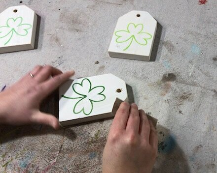DIY craft kit for adults. How to make mini wood tags for St. Patrick's Day using your Cricut. How to stenicil wood signs for spring. How to distress handpainted wood signs using sandpaper.
