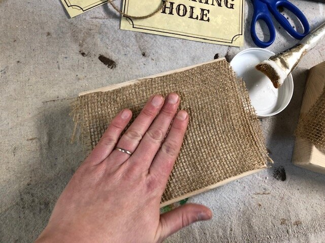 How to apply fabric and burlap to wood. Watering hole wild west table sign. DIY western party table decor. Free printable