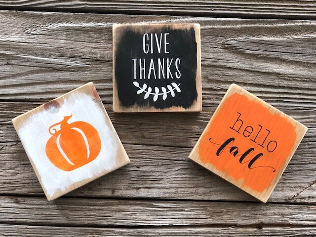 DIY painted fall signs. How to make your own farmhouse style signs for your fall themed decor. These painted tiny signs are so perfect for coffee bars, tiered trays and mantles. This trio of hello fall, give thanks, and a pumpkin are hand painted in orange, black and white, the classic fall colors. This tutorial will take you step by step on how to make your own stenciled wooden signs at home.