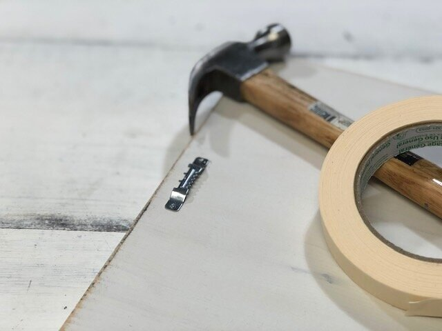 How to attach a sawtooth hanger to a wood sign. Quick and easy way to put hanging hardware on a sign to hang. Use masking tape to hold your sawtooth hanger in place before you hammer it down.