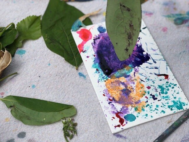 How to paint with nature, a fun outdoor craft to do with your kids. Paint on a dollar tree canvas with nature using food coloring, flowers, twigs, leaves.