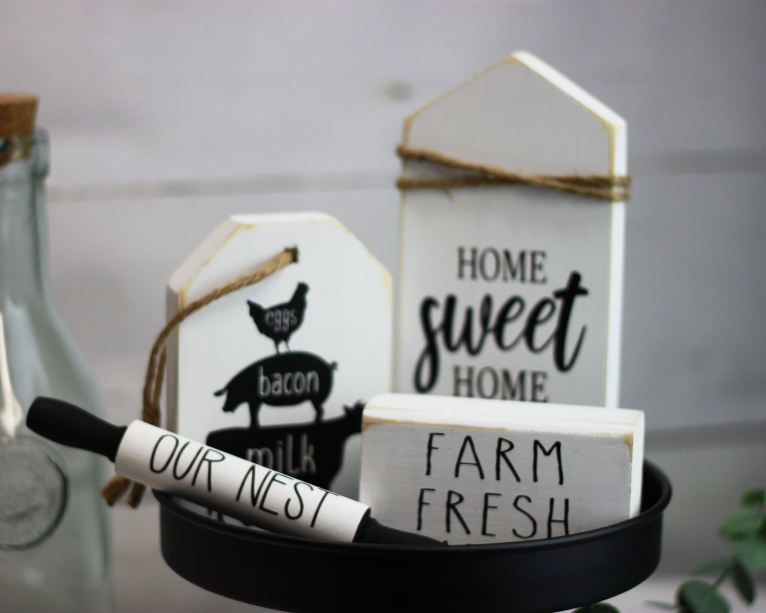 Tiered tray signs for rustic home decor. Classic style mini wood signs in white and black. Sign bundle comes with home sweet home, farm animal trio of chicken pig and cow on a rustic wood tag, mini rolling pin our nest, and farm fresh.