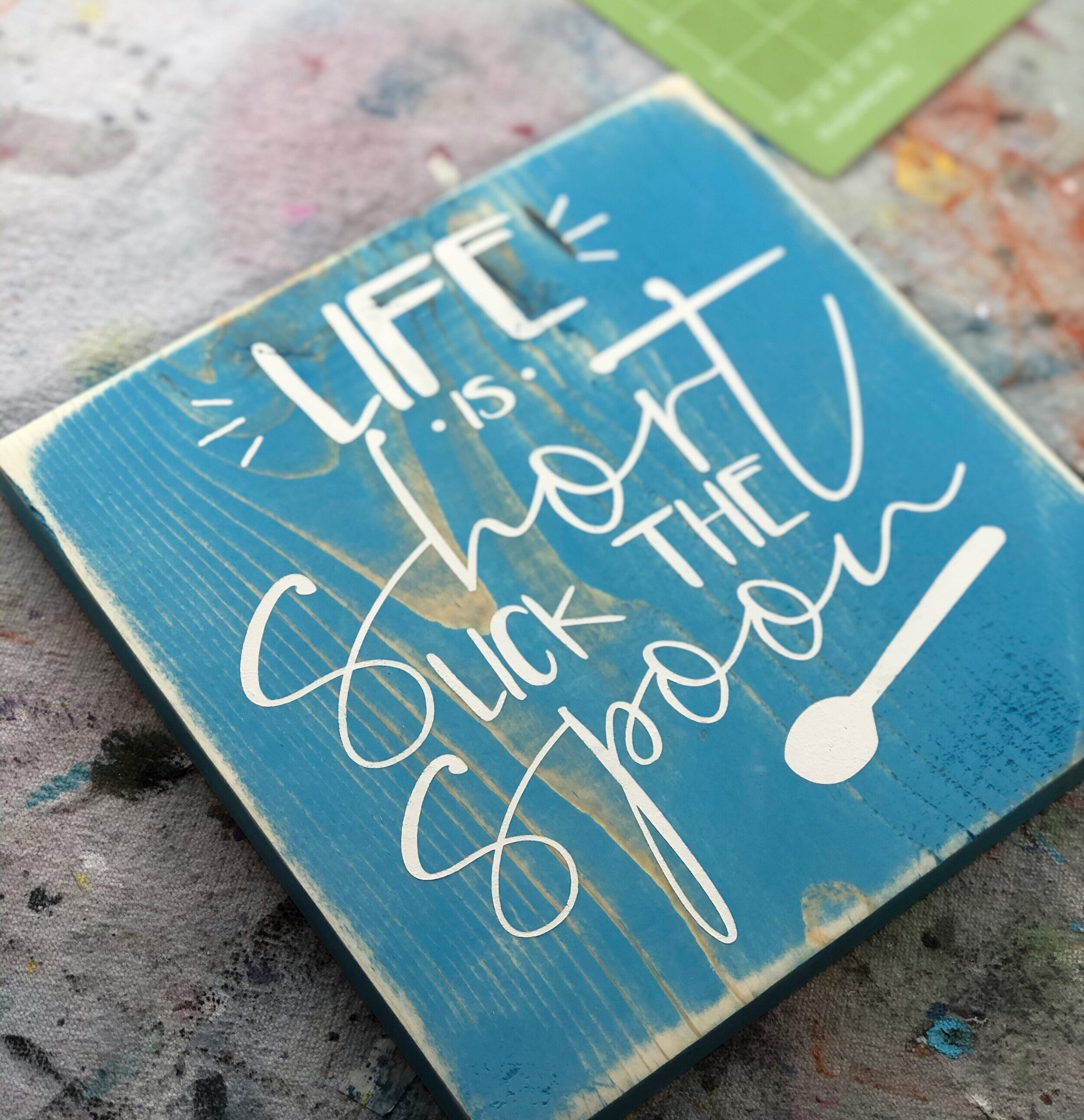 Life is short lick the spoon wood sign. How to paint a wooden kitchen sign with a humorous saying. Stained aqua sign with a white stenciled saying