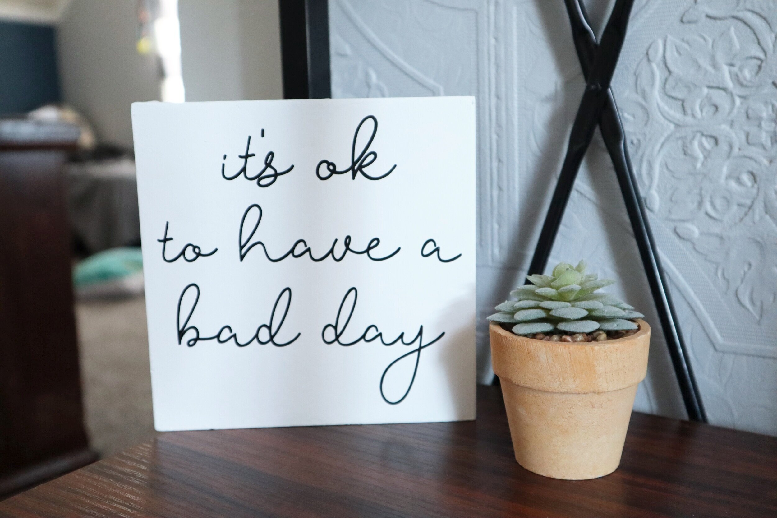 DIY dollar store sign makeover. How to give a dollar tree seasonal free standing faux wood sign a more modern look using your Cricut. DIY vinyl decal using your Cricut 'it's ok to have a bad day' diy sign.