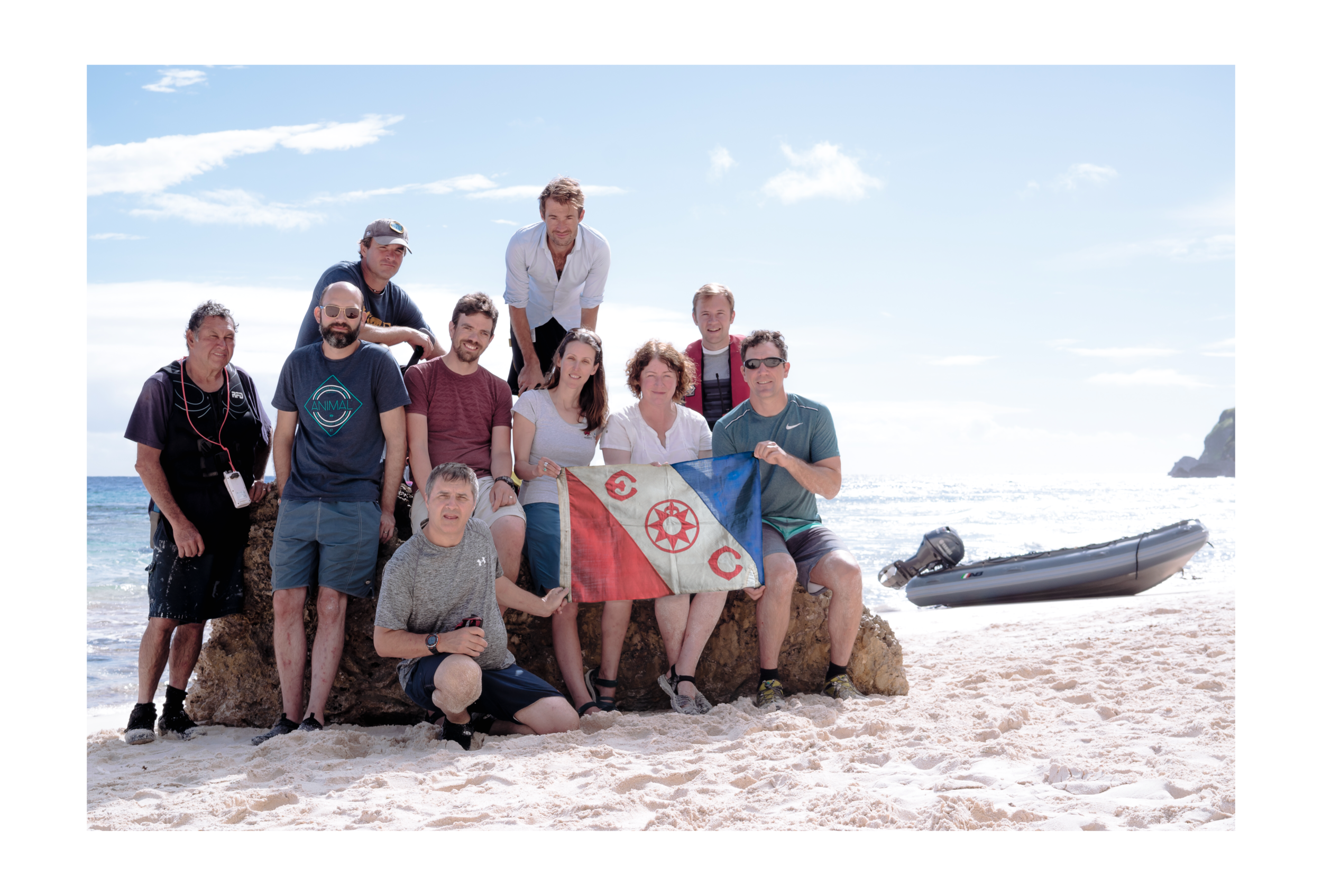 Expedition team with The Explorers Club Flag #97 on the Northwest Beach of Henderson Island