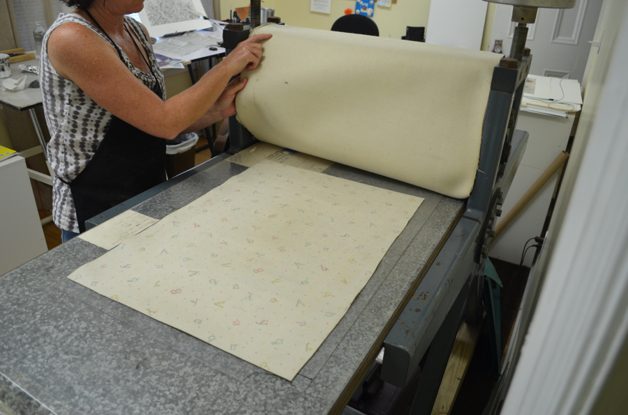 - The press blankets are laid over the paper and plate.