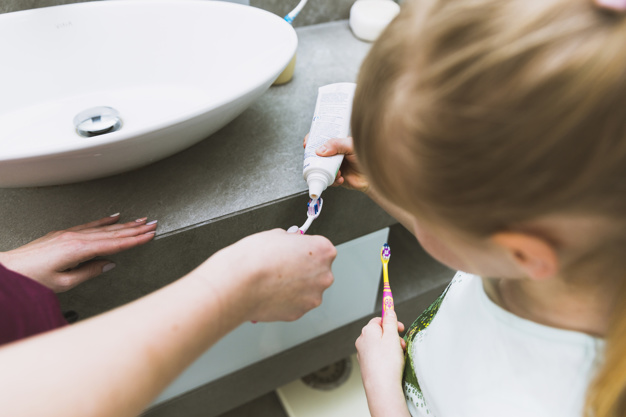 girl-putting-toothpaste-on-brush-of-mother_23-2147807829.jpg