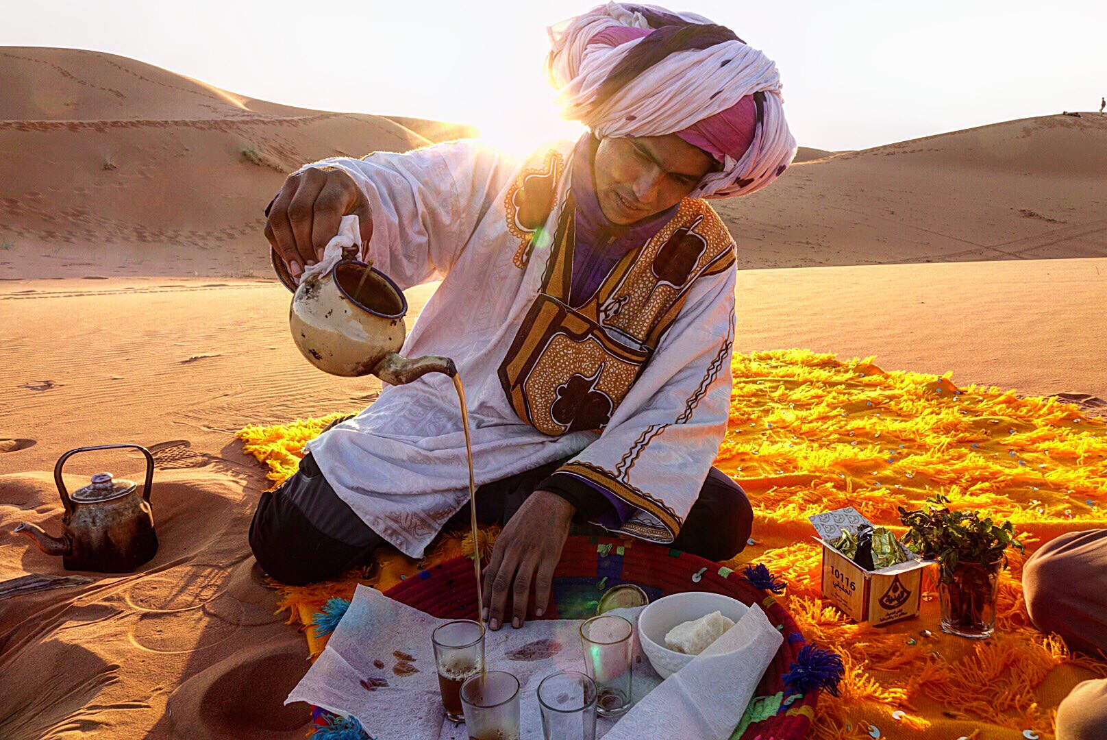 HASSAN SET UP A SPECIAL TEA SPOT TO ENJOY THE SUNSET IN THE SAHARA DESERT.