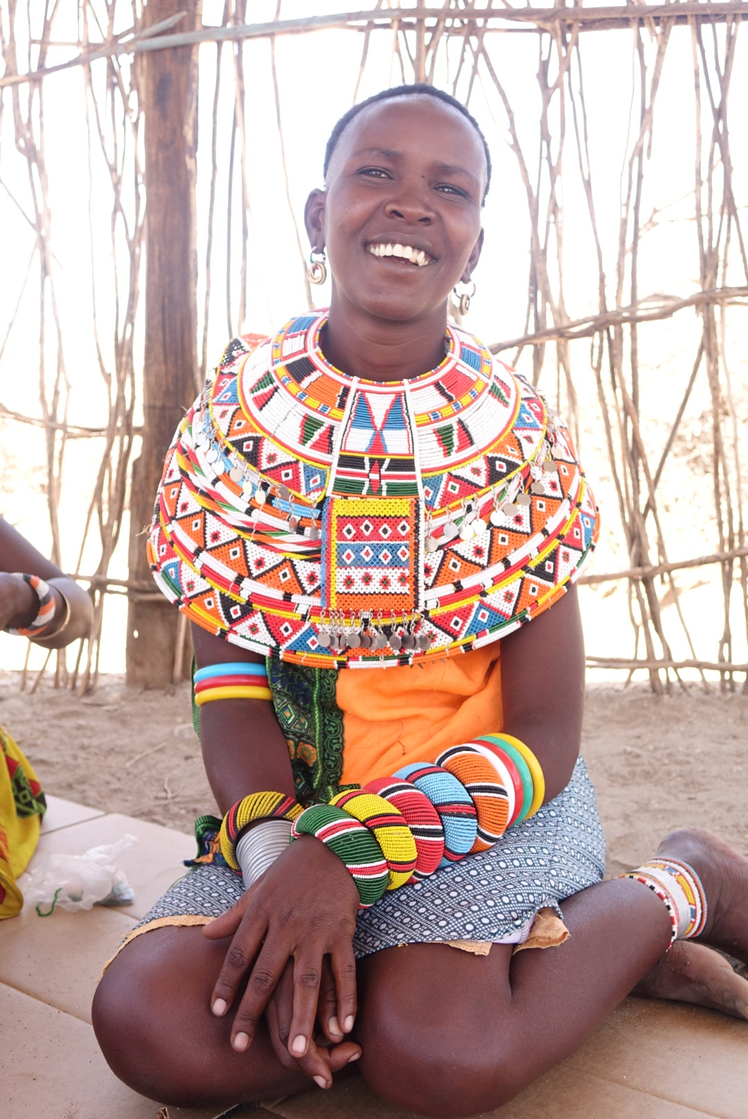 Alice is a skilled beadwork jewelry artist. The traditional necklaces she is wearing here can take anywhere from 2 - 4 months to make. The bracelets, cuffs, and bangles take around 3 weeks. - SUPPORT ARTISTS. THINK GLOBAL. EMPOWER WOMEN.