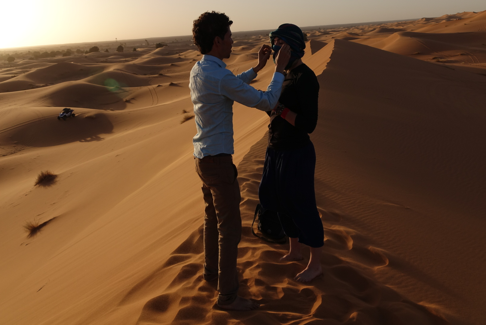 Mbarek fixing Brooke's scarf in-between takes before a sand storm.