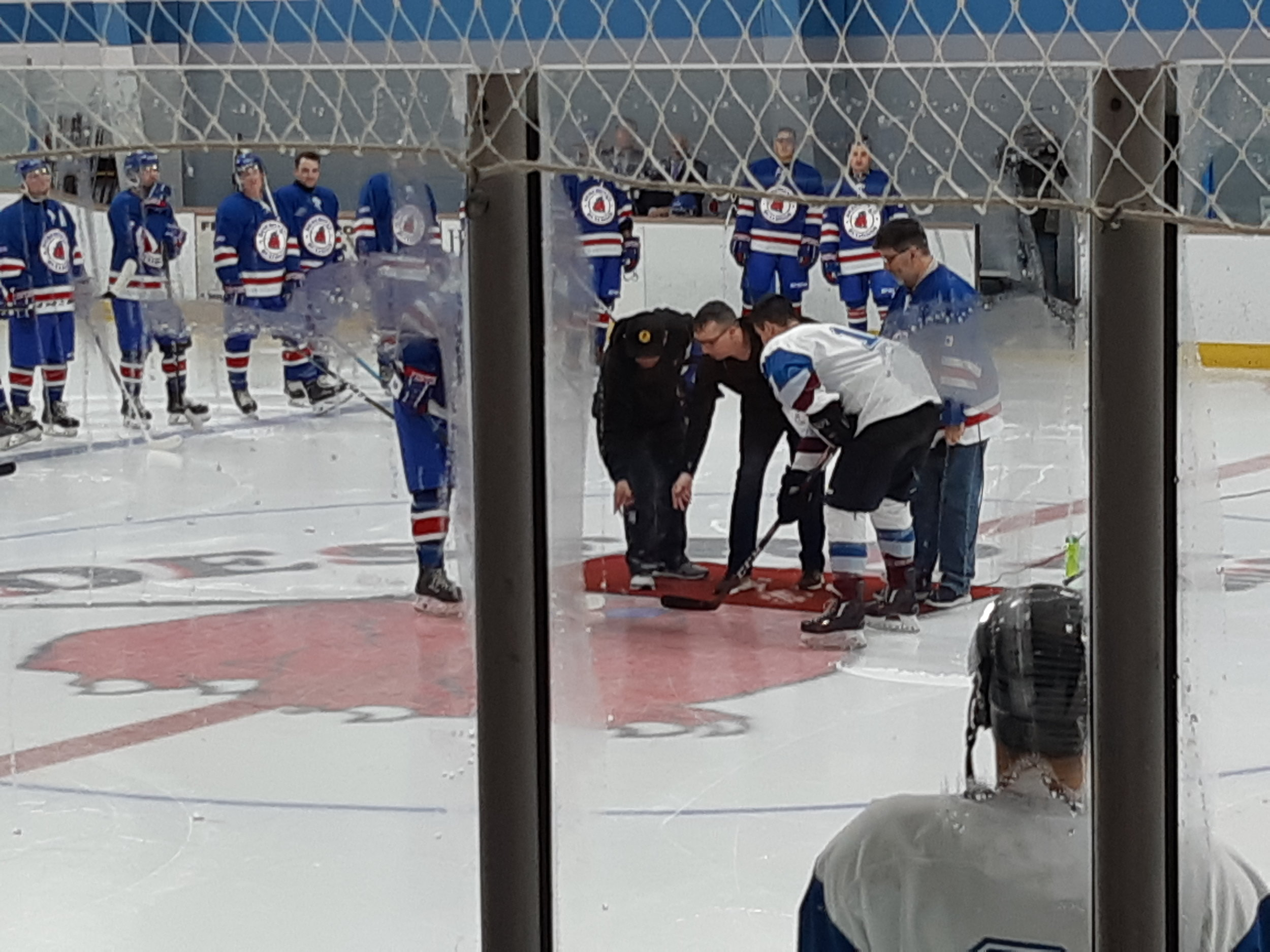 """Mayor Dan Johnston at centre ice, drops puck at Deseronto Senior 'A"""" hockey home opener. With (l) Bob Greenwood, Team Sponsor, and (r-standing), Richard Crouse, Bulldogs Game M.C. and Announcer."""