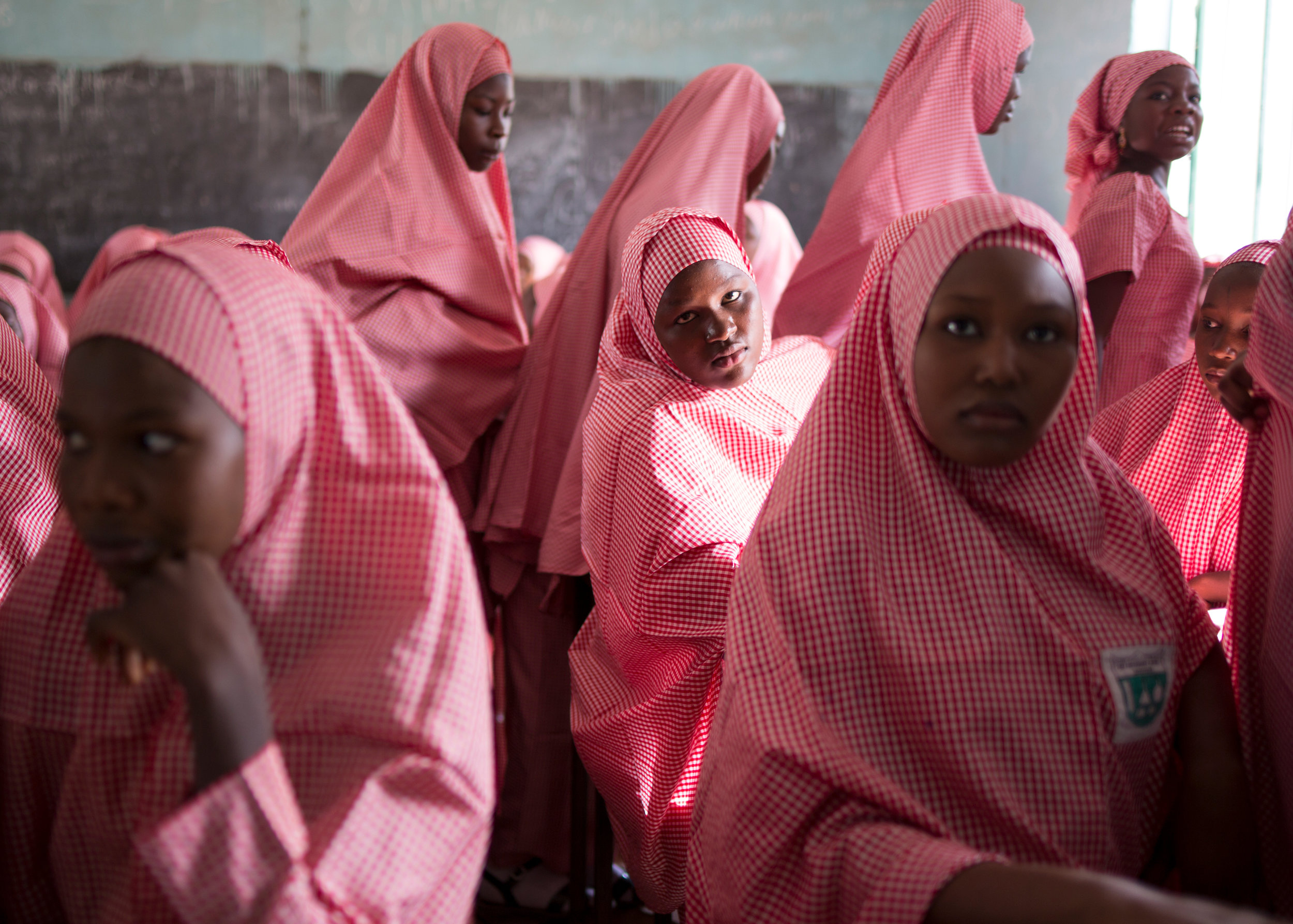 """Students wait for class to begin at Shehu Sanda Kyarimi government school"". Education is Forbidden series. Maiduguri, Nigeria, 13"" x 18"", 2016."