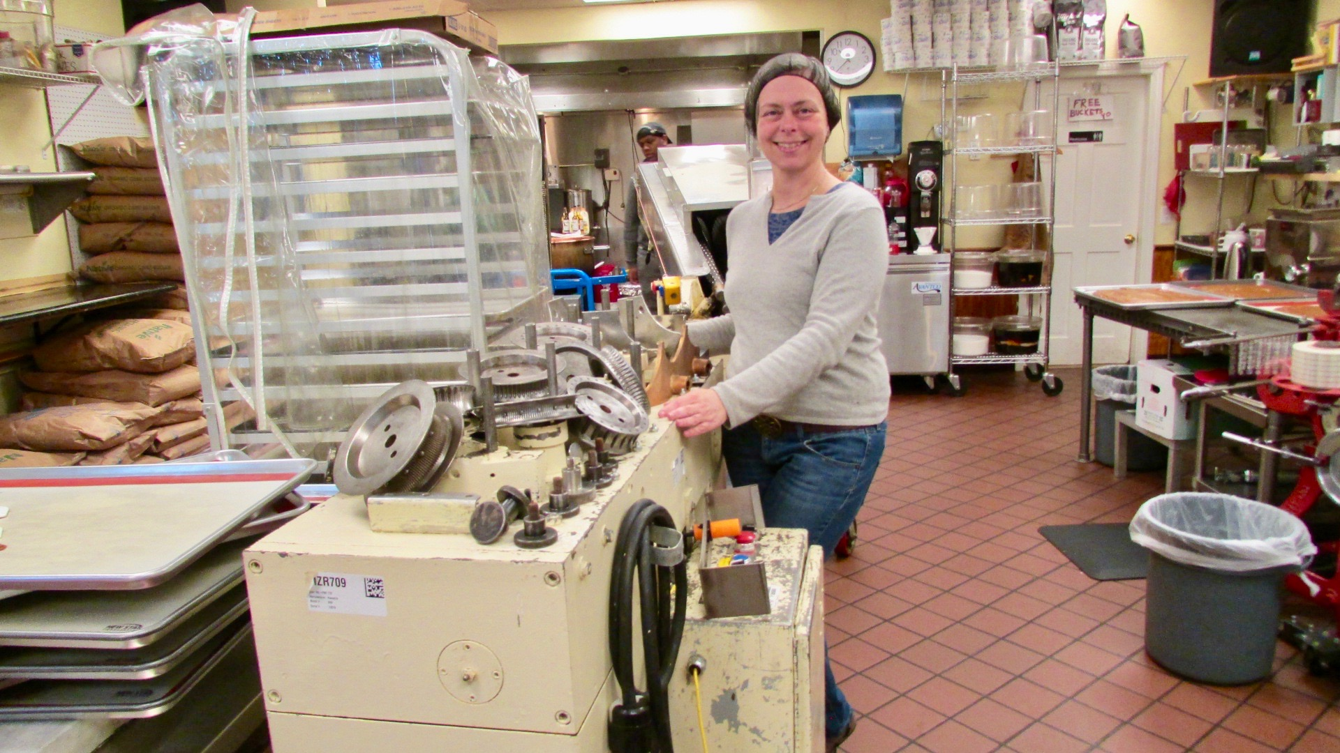 Co-Founder, Kate McCrea, poses with their newest piece of machinery, a used caramel wrapper, which will increase the production of wrapping by 3x.