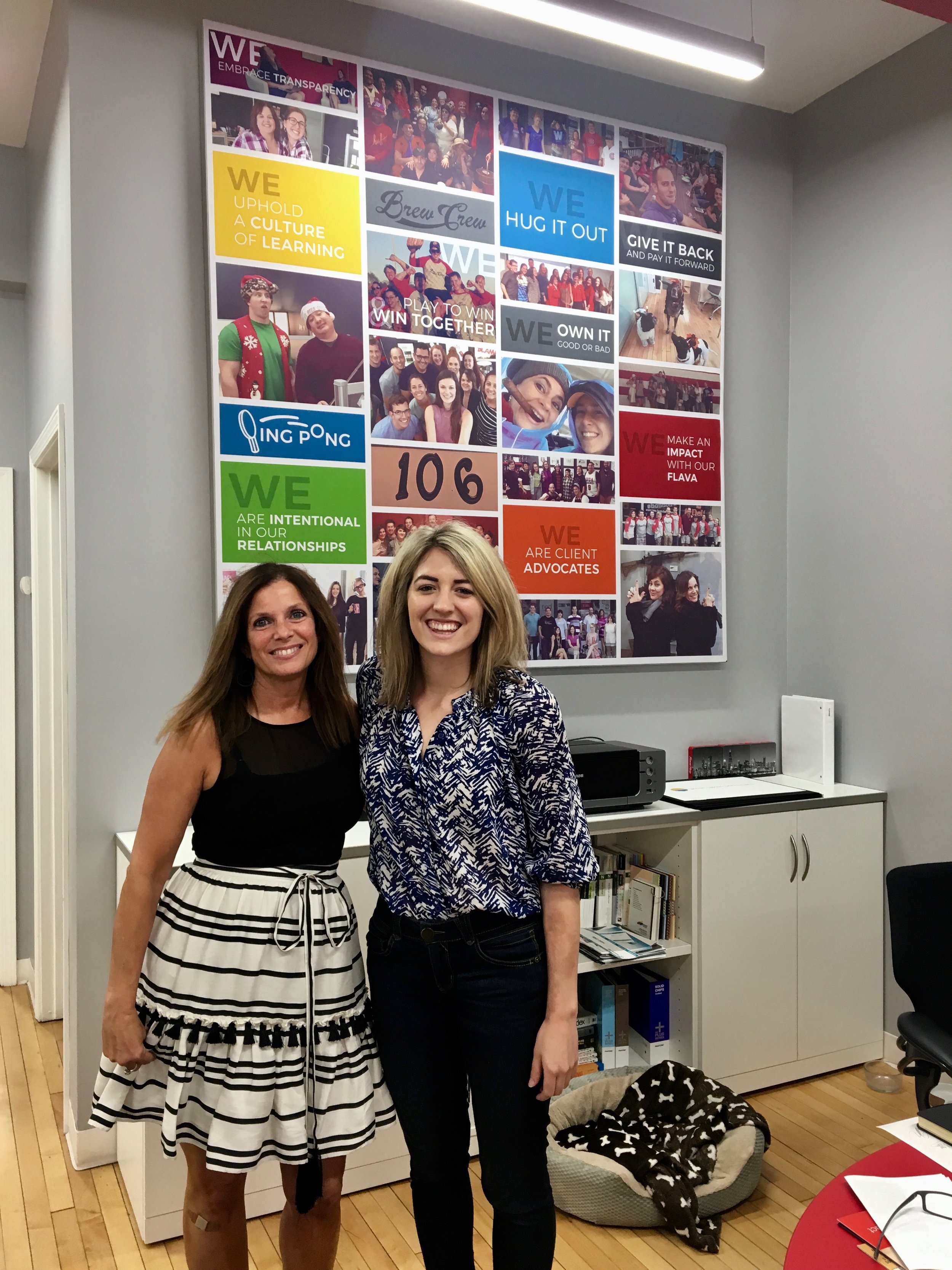 Kathy Steele and Julia Kortberg pose in front of the values-wall.