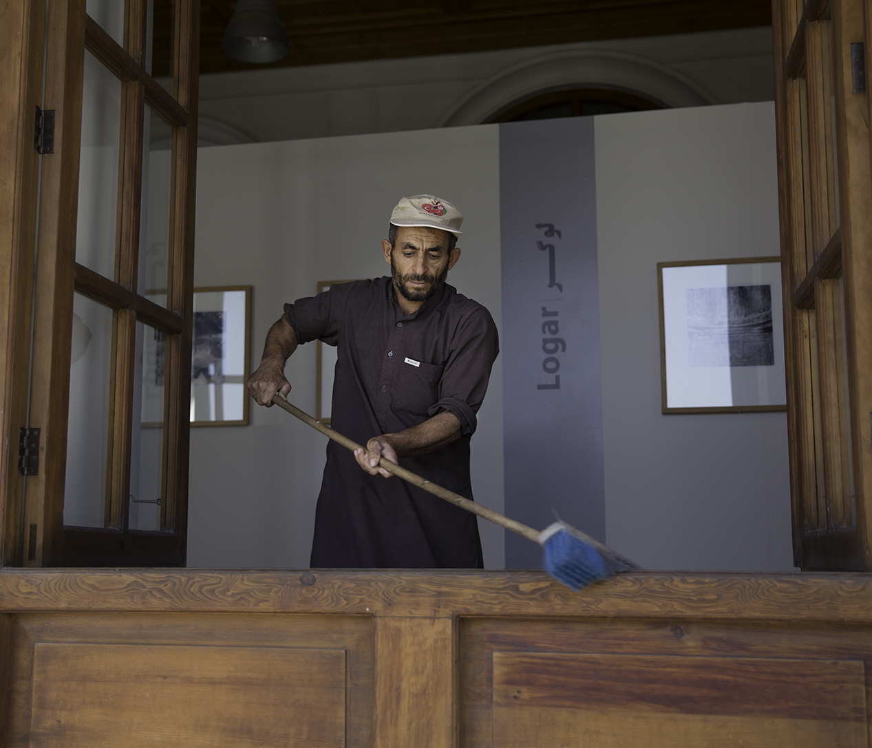 An employee sweeps the window ledge inside a gallery and exhibition hall in Bagh-e Babur's main pavilion. The gallery pictures were taken by Josephine Powell in the 1960's of Afghanistan's historic monuments.
