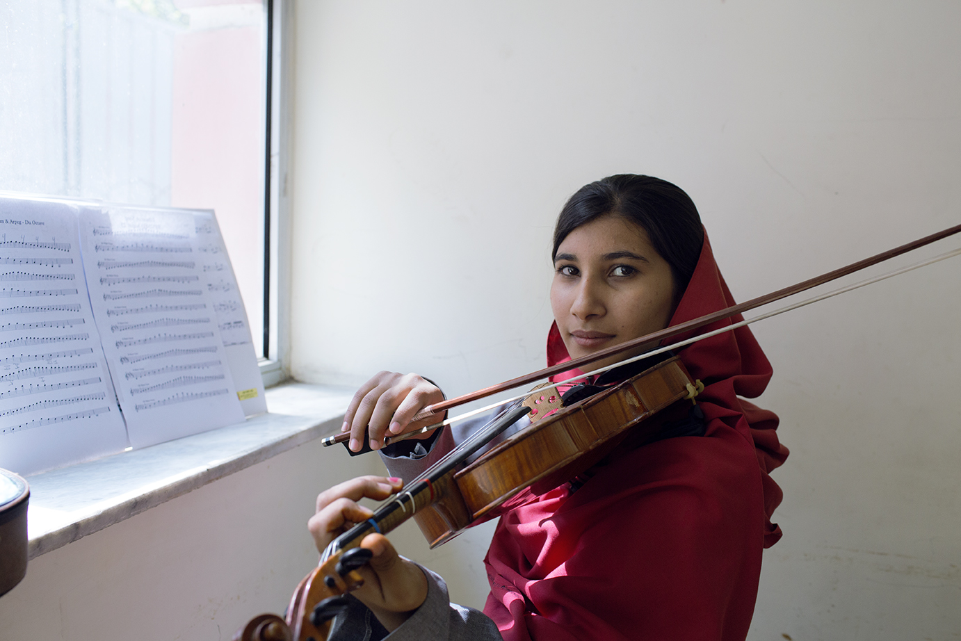A young woman practices the violin.
