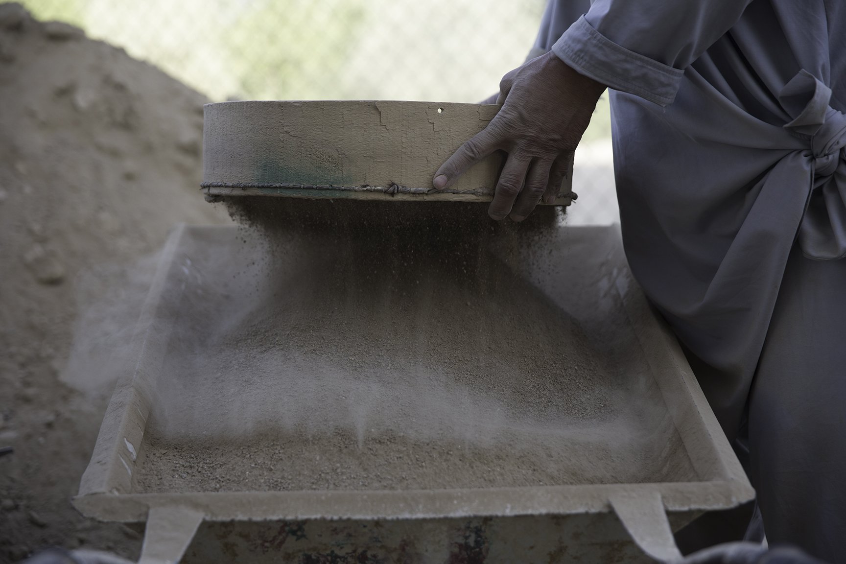 A laborer sifts and screens dirt to be used when mixing concrete.