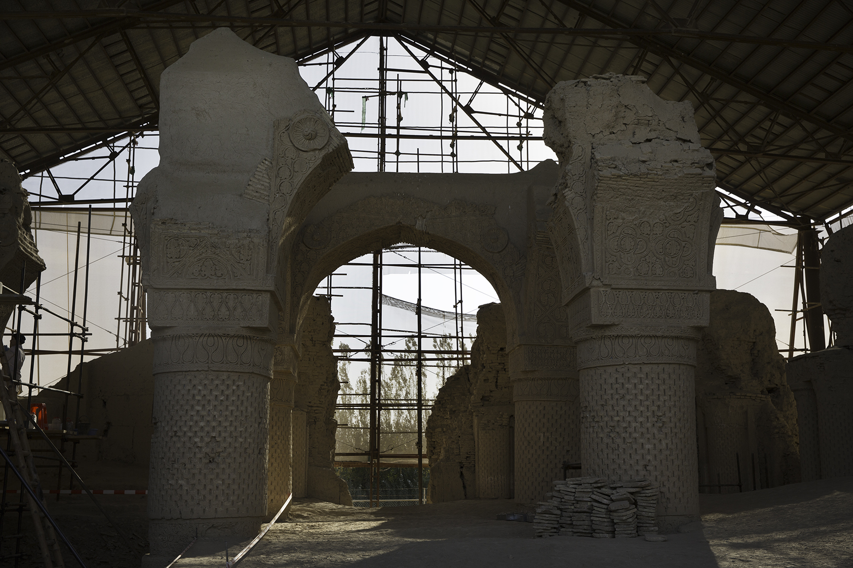 Six pillars preserved by a French restoration team stand underneath a protective roof. The dirt floor made up of collapsed tiles from the roof will be un-earthed.