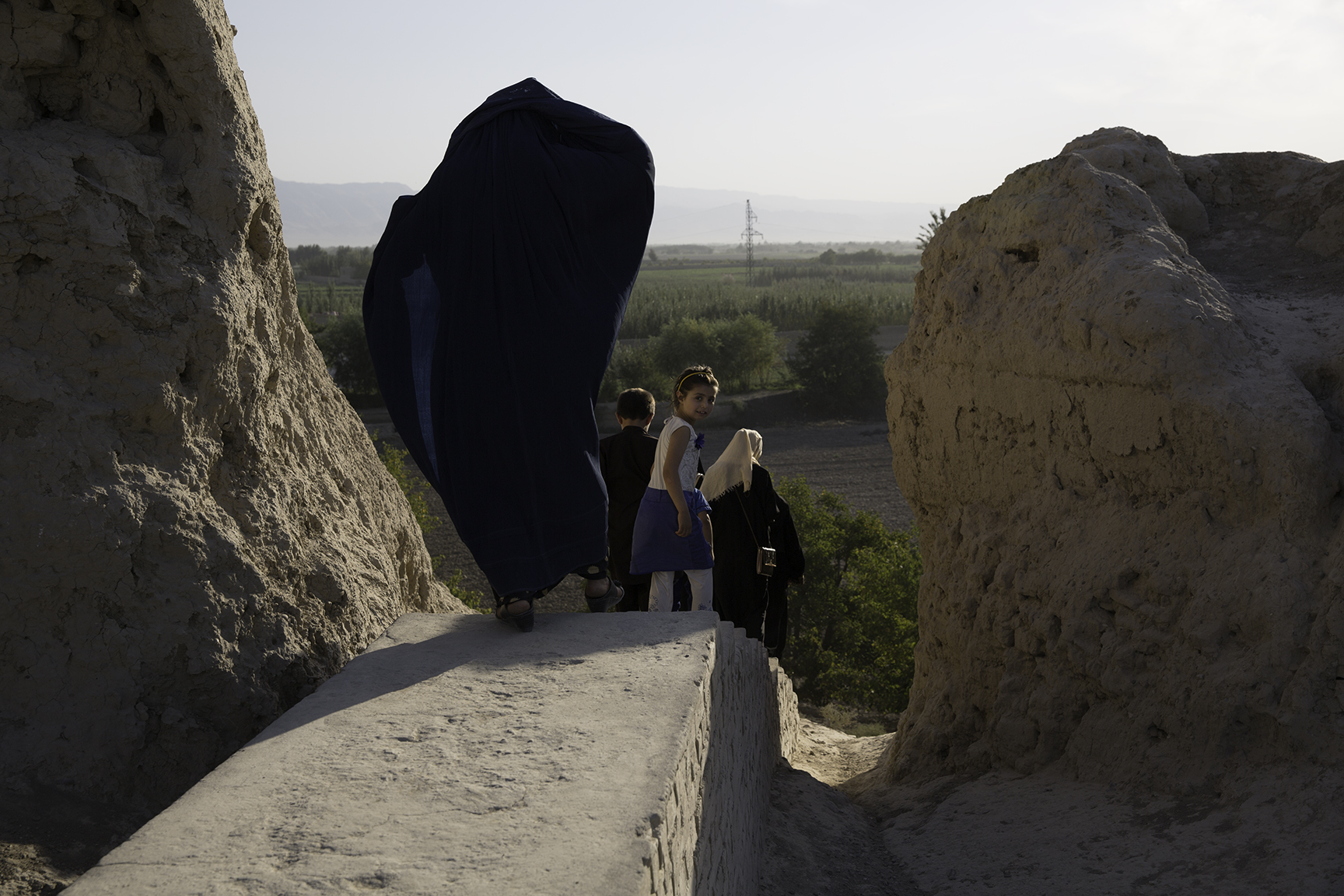 Women stride along Balkh's earthen wall, not far from the shrine of Rabaya-e-Balkhi, a famous woman poet of the Samanid dynasty (ninth–tenth century CE) who was killed after her brother discovered her love for a slave.