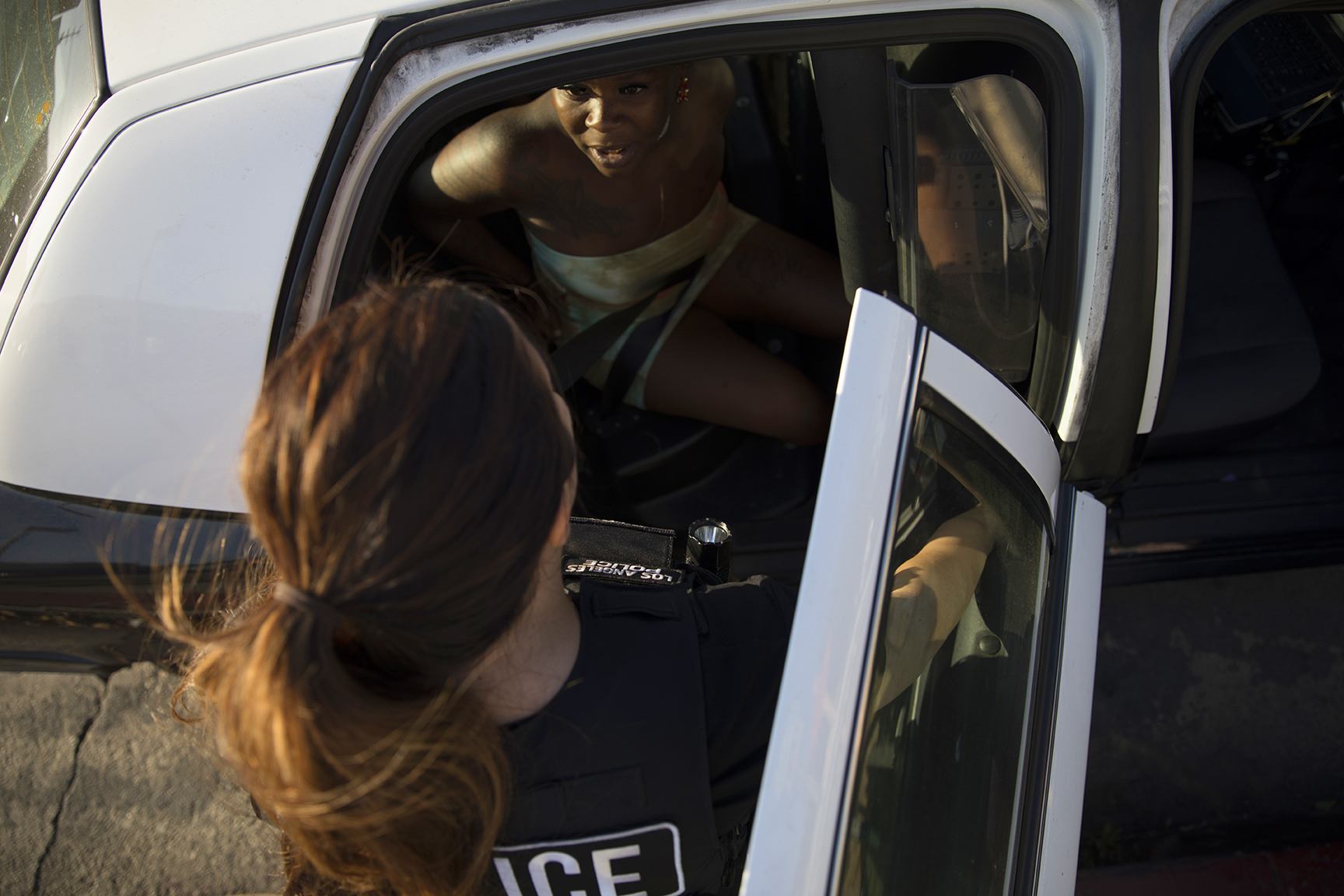 May 22, 2017: A woman arrested for prostitution, center top, speaks to an officer from the Los Angeles Police Department's vice squad in the southern area of Los Angeles, California. The woman was arrested for soliciting an undercover police officer for the purpose of prostitution, a misdemeanor charge.