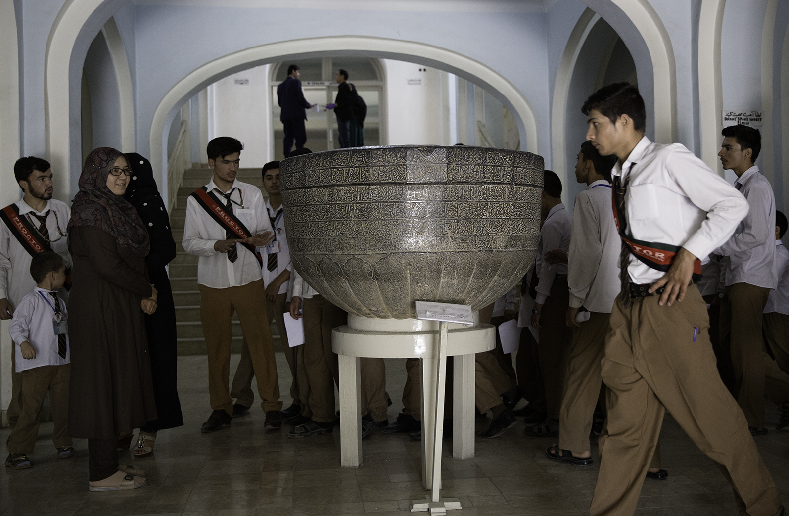 Schoolchildren cluster around a black marble basin carved with Islamic inscriptions from the late fifteenth century CE. A lotus blossom chiseled on its underside led scholars to believe that the basin originally might have been Buddhist and centuries older.