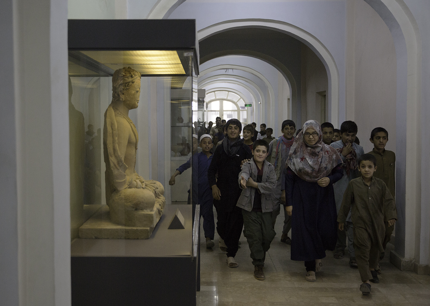 At the National Museum of Afghanistan, children file past a clay statue of a sitting Bodhisattva (third to fourth century CE from Tepe Maranjan outside Kabul) that was painstakingly repaired after the Taliban smashed it.
