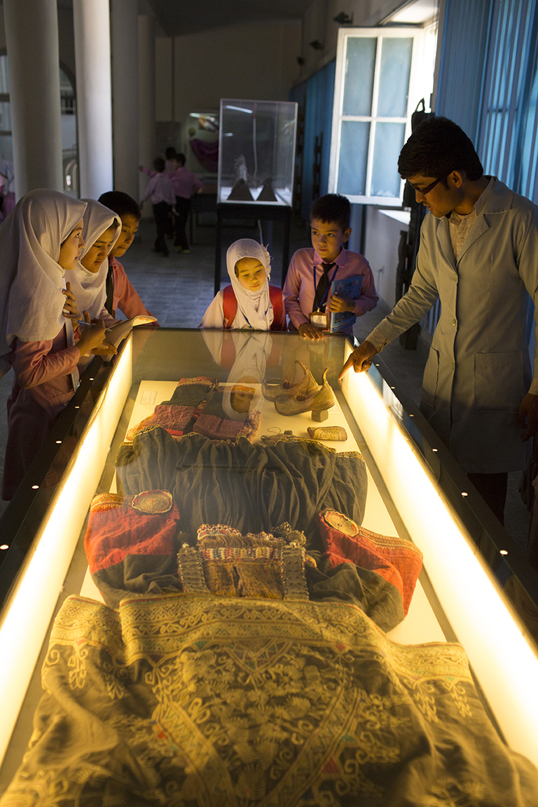 Schoolchildren gaze at one of the museum's many rich ethnographic displays, exhibiting the traditional dresses, jewelry, and costumes worn by Afghanistan's many ethnicities.