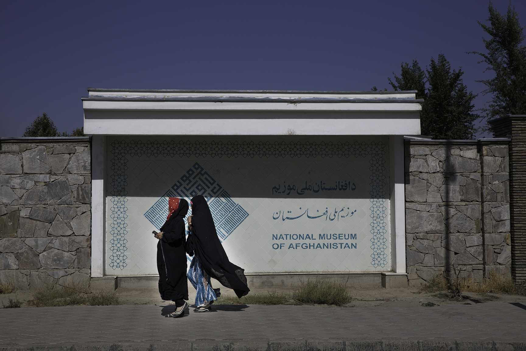 Two women pass by a sign for the National Museum of Afghanistan located near the visitors' center in the museum's garden. The sign is written in Dari, Pashtu, and English.