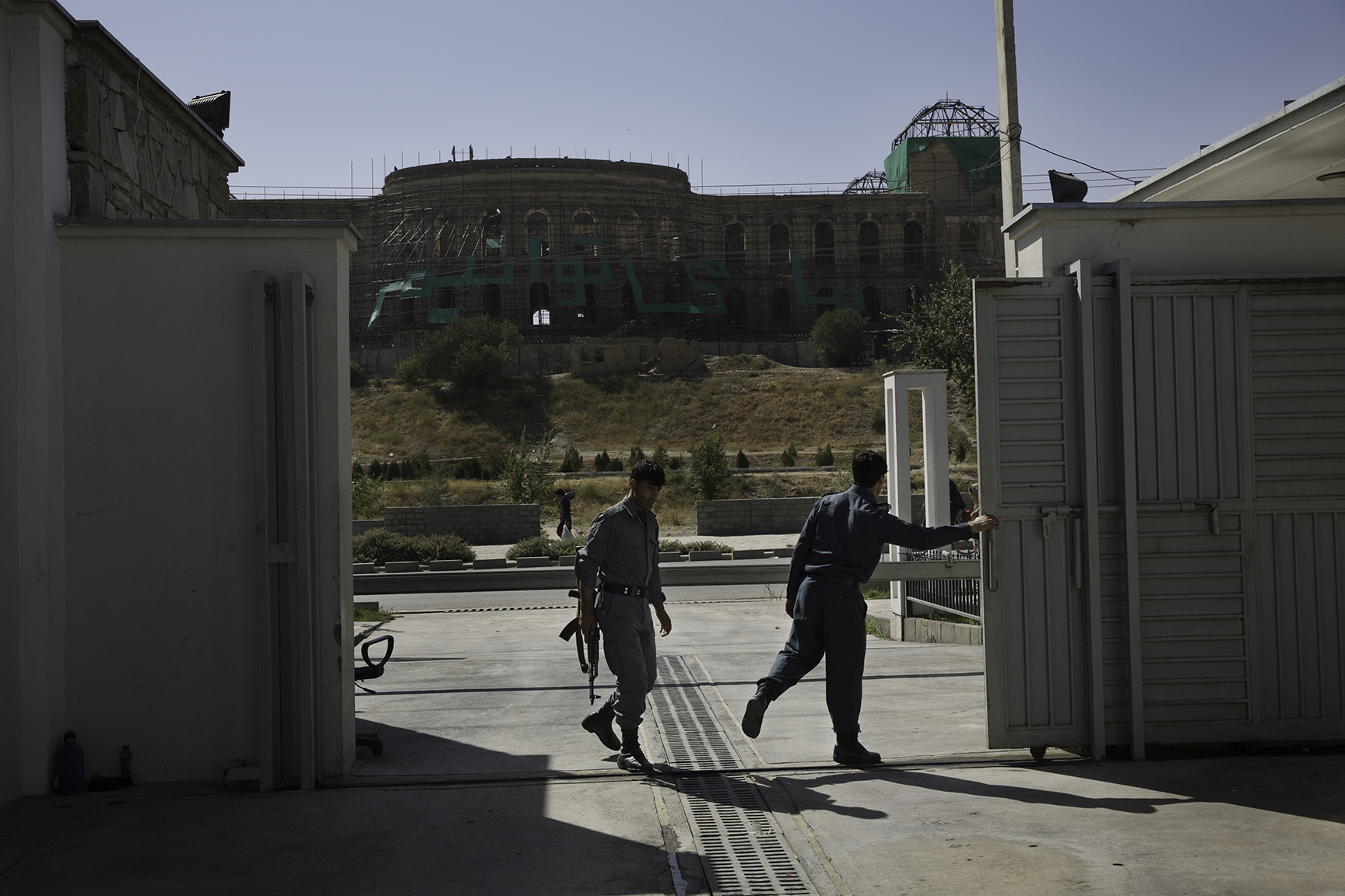 Two National Police officers open the metal gates to the National Museum of Afghanistan. This entrance, which looks across to Darulaman Palace, was installed in 2013 with funds from the U.S. Embassy, Kabul, to enhance security of vehicles entering the museum grounds.