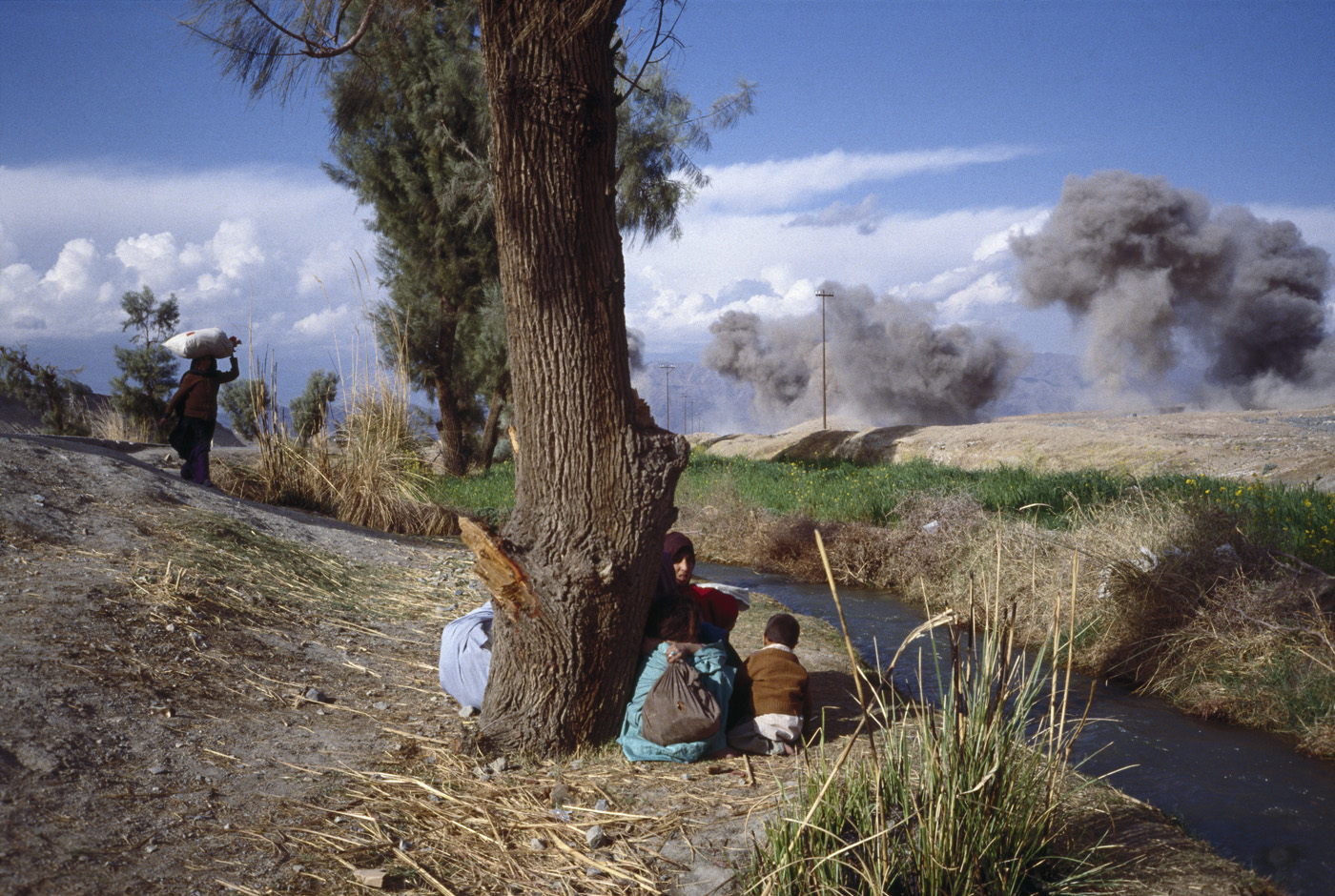 March 1989: Afghan refugees take cover from a bombing attack by the Afghan Air Force during the battle for Jalalabad.