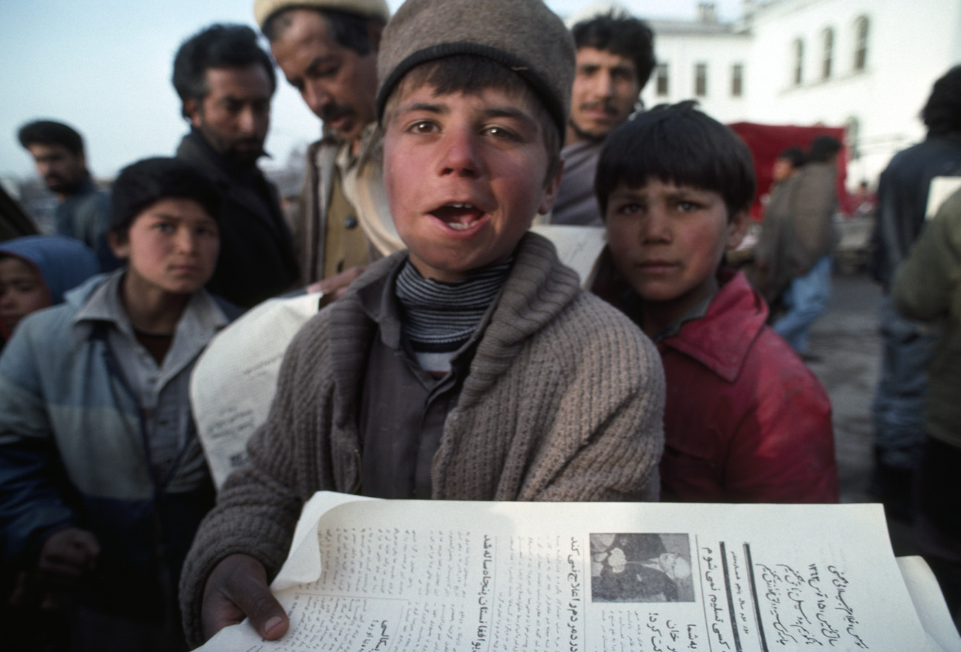 March 1992: A young boy sells government-owned newspapers on  a Kabul street.