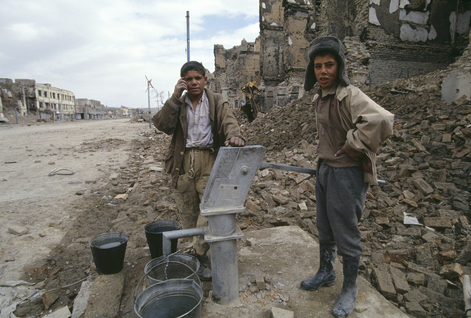 March 1994: Boys working with government militiamen fill water buckets from a hand pump on Jade Maiwand, Kabul's former business district and a front line between factional groups. Food, water and fuel were retrieved during short-lived periods of peace.