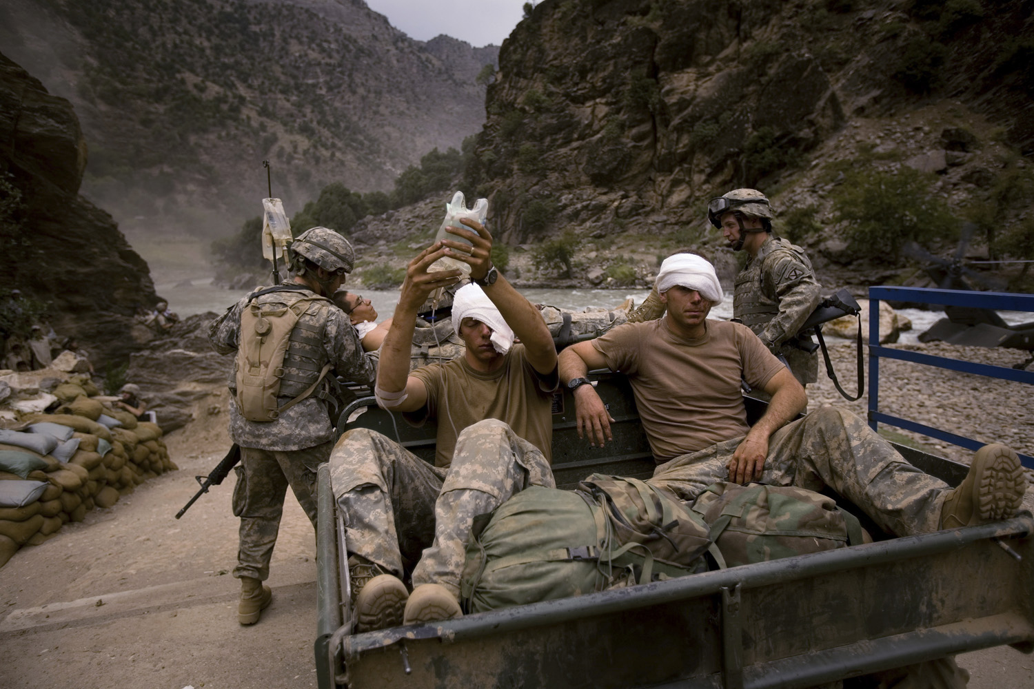 August 2006: Three wounded U.S. Army soldiers from the 10th Mountain Division await evacuation by helicopter from Kamdesh, Nuristan province. They were ambushed and suffered wounds to their eyes and foreheads.