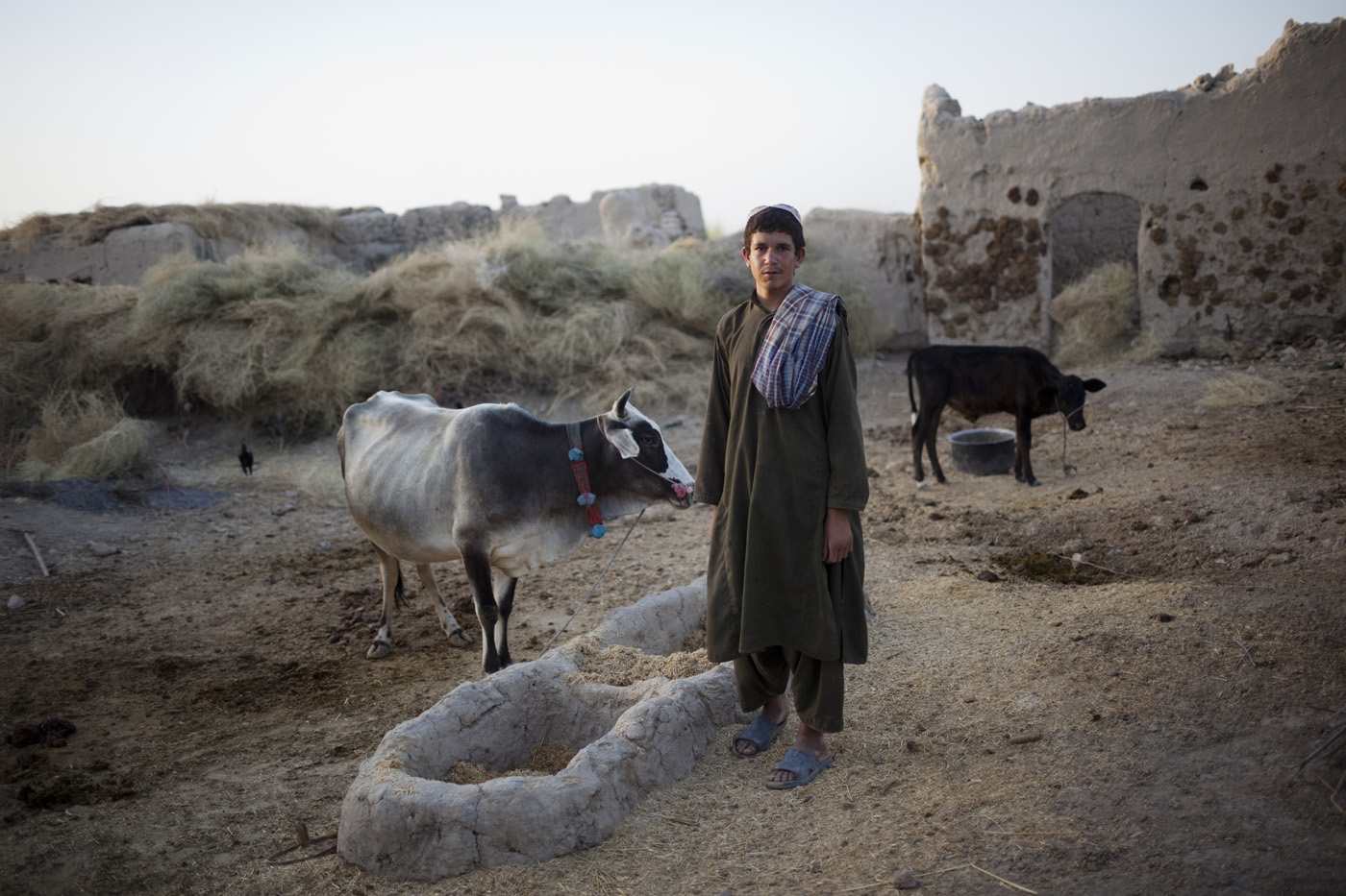 August 2009: An Afghan farmer stands outside his home as a U.S. Marine patrol walk past in Khan Neshin, Helmand province.