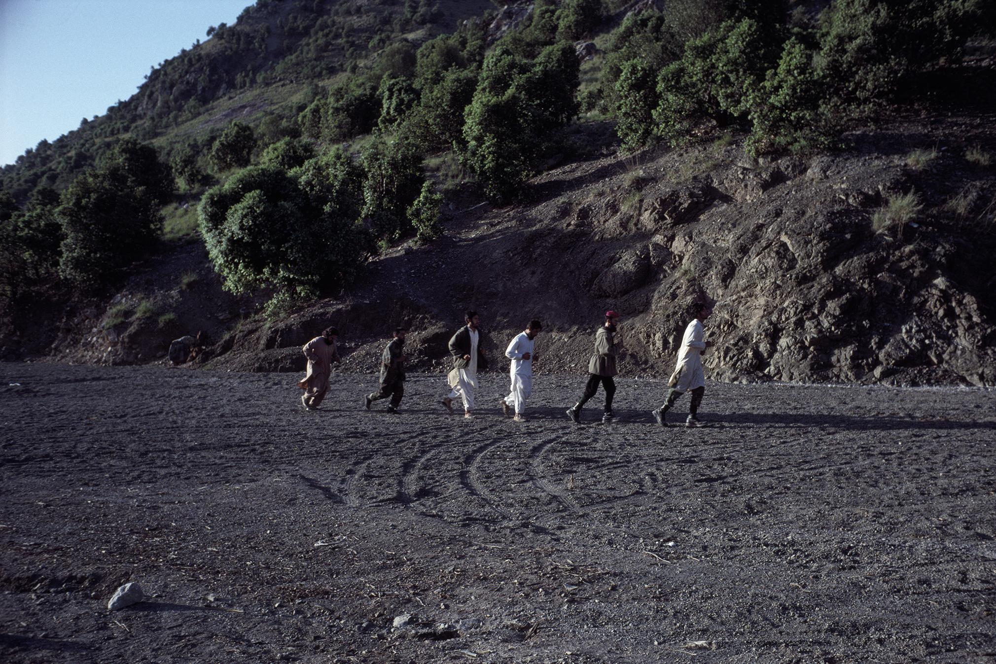 May 1990: Arab Al Qaeda members and Afghan mujahideen jog at a Zhawar training camp outside of Khost, Afghanistan.