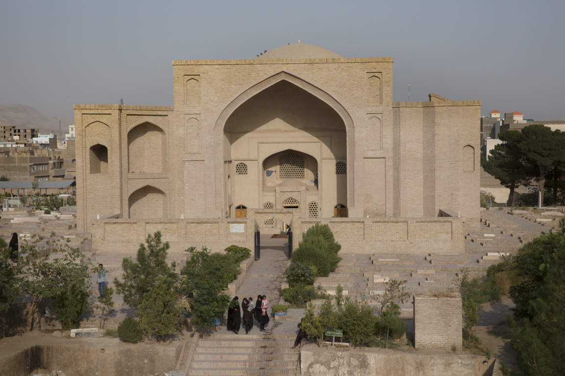Women and children leave Shahzada Abdullah in Khuandiz, in the historic center of Herat, once capital of Central Asia. Under the patronage of Queen Gowhar Shad, the daughter-in-law of Tamerlane, Herat was a center of arts and learning in the fifteenth and sixteenth centuries CE. Clad in plain-fired brick, the tomb's exterior is graced with ogee portal arches.