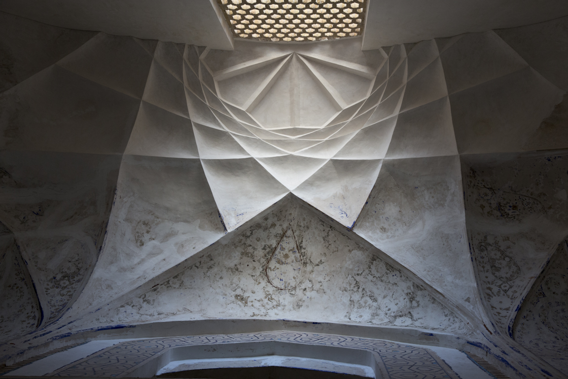 Sunlight filters through an original fire-brick lattice screen, illuminating an intricate geometry of lines in the  karabandi  style, inside Shahzada Abdullah's mausoleum.