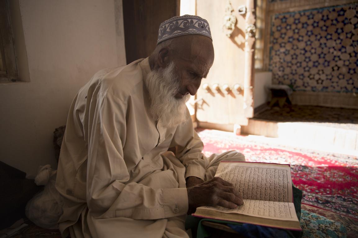 A man reads from the Koran in a quiet corner of Shahzada Abdullah's mausoleum in Herat.