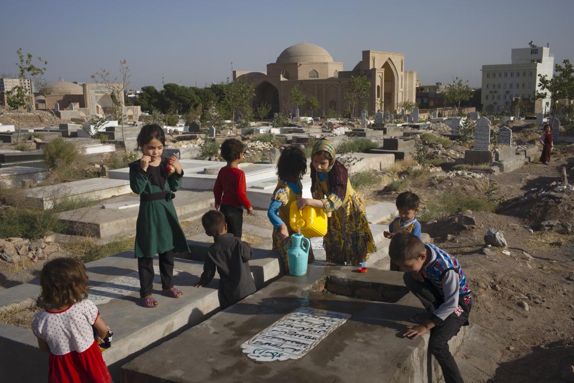 Herati children clean the gravestone of their grandparents, buried outside the Shahzada Abdullah mausoleum in Herat, Afghanistan. Families traditionally clean the gravestones of their ancestors before the  Eid al-Adha  (Festival of Sacrifice).