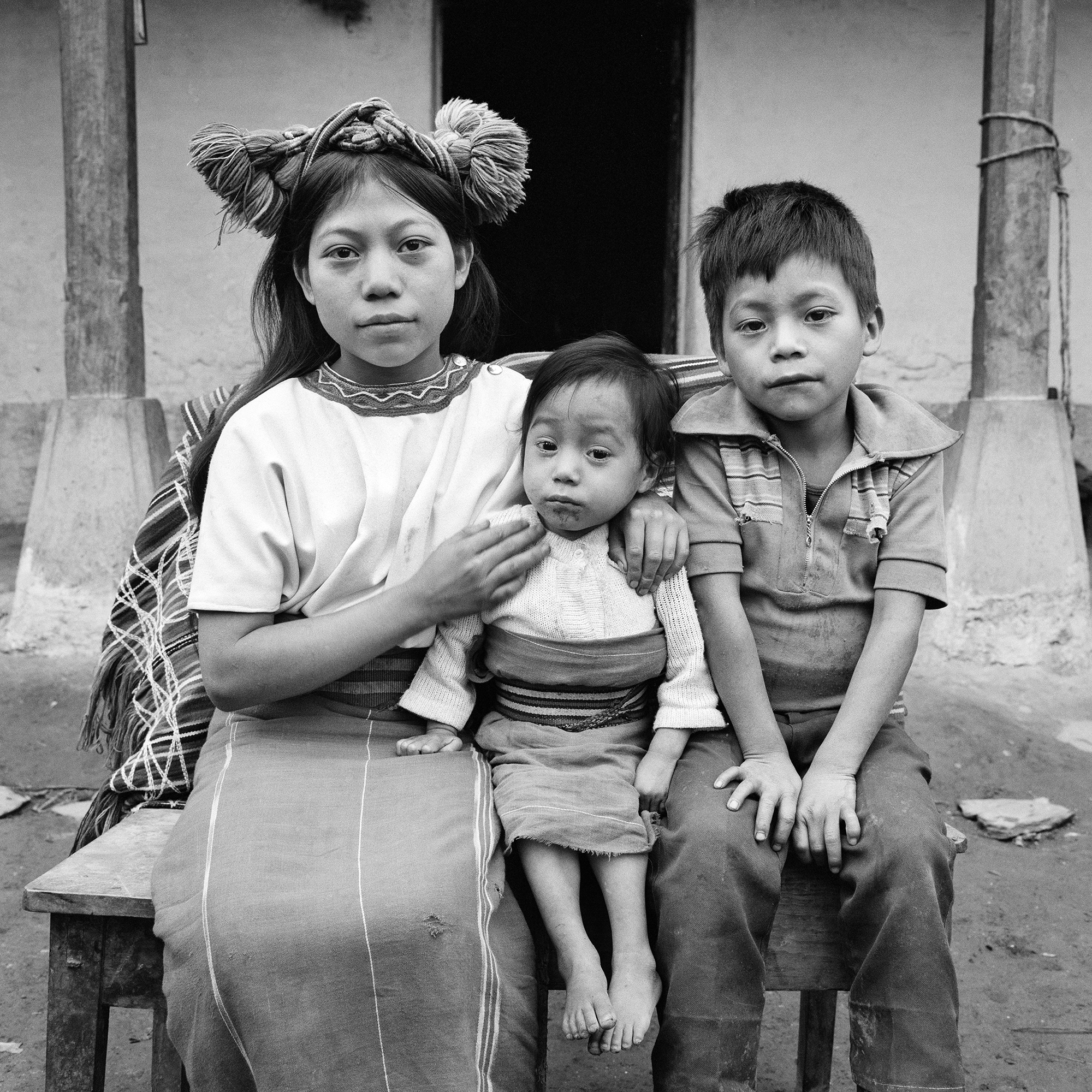 A young Ixil Maya girl wearing a traditional head dress, left, sits for a picture with her brother and sister in Nebaj, Guatemala, January 1, 1984.