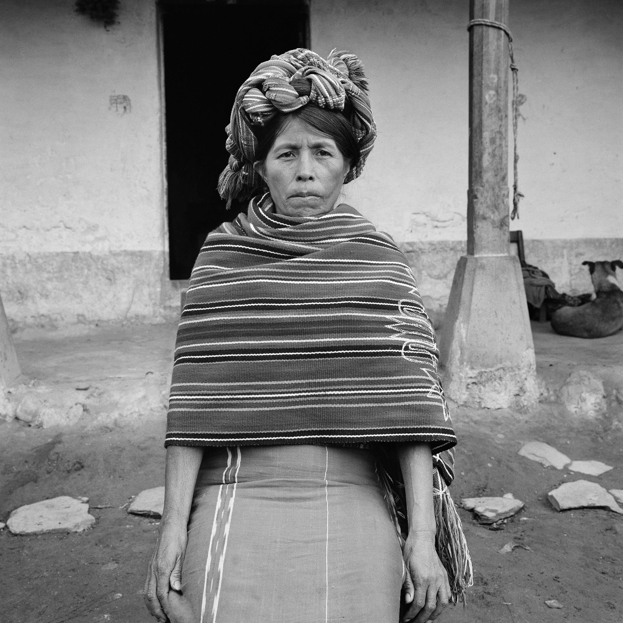 An Ixil Maya woman wearing a traditional head dress sits for a picture in Nebaj, Guatemala, January 1, 1984.