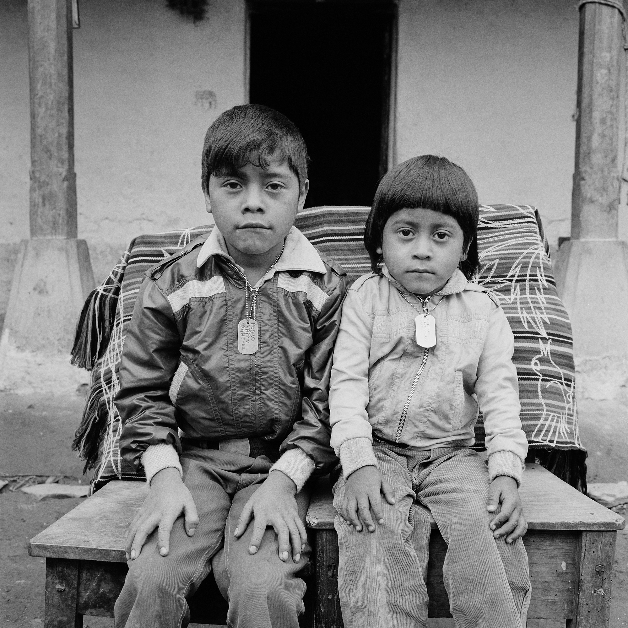 Two Ixil Maya brothers wearing name tags sit for a picture in Nebaj, Guatemala, January 1, 1984.