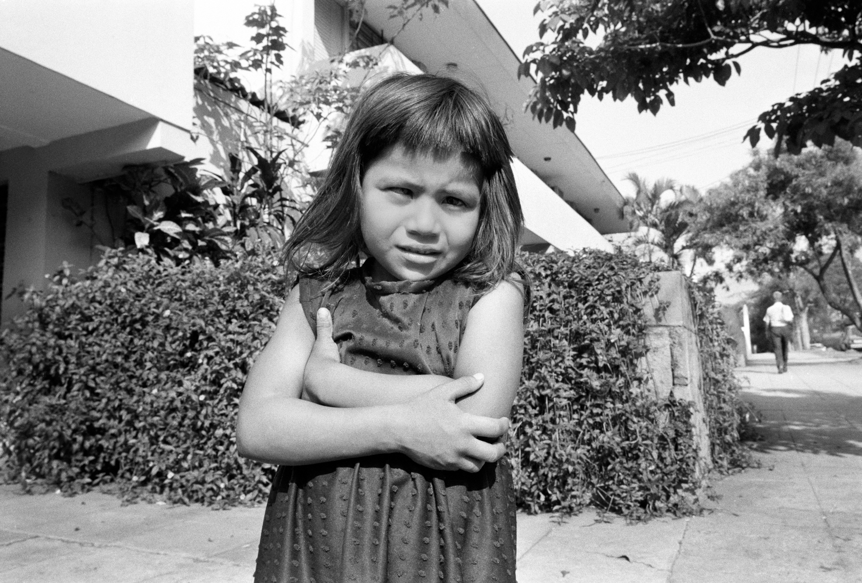 A girl stands on the sidewalk April 1983 in the Escalon neighborhood of San Salvador, El Salvador.