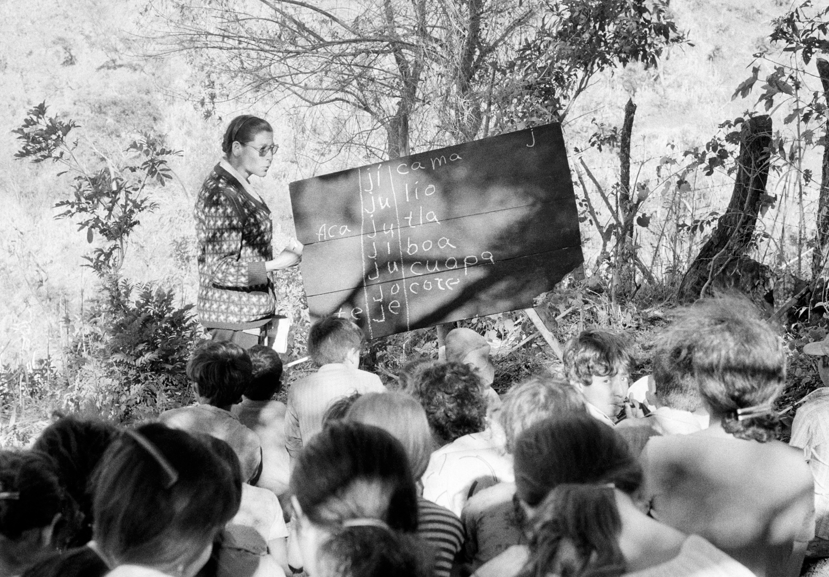 In territory held by Popular Liberation of Forces (FPL) guerrillas, students attend an outdoor grammar class February 22, 1981 near Santa Anita, Chalatenango department, El Salvador. The children had been displaced by the ongoing conflict between guerrilla factions and government forces. At the time, the country was engaged in what became a 13-year Civil War between successive right-wing governments (backed by the US and others) and various armed guerrilla factions that eventually claimed over 75,000 lives before ending in 1992.